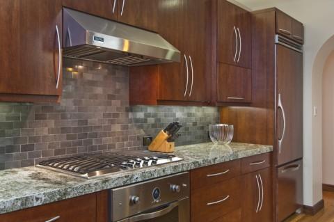 Mặt trước của tủ lạnh được bọc bằng gỗ trùng với gỗ của tủ bếp. Thậm chí tay nắm cửa tủ lạnh cũng đồng dạng với tay nắm tủ bếp.