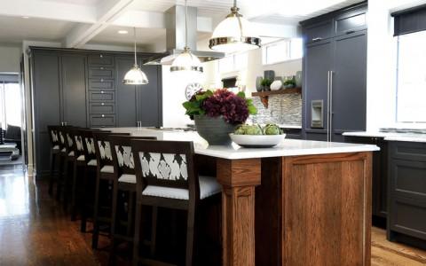 Tủ lạnh màu đen và tủ bếp màu đen phối hợp cùng đảo bếp bằng gỗ và hàng ghế duyên dáng là tâm điểm của căn bếp.
