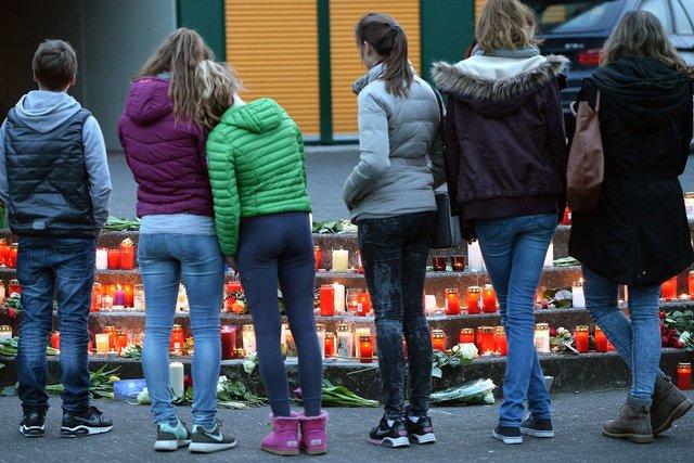 Các học sinh đứng cầu nguyện cho những nạn nhân xấu số ở trường trung học Joseph Koenig Gymnasium