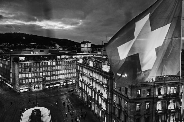 Lá cờ Thụy Sĩ tung bay trên nóc Savoy Baur en Ville -khách sạn xa xỉ nhìn xuốngParadeplatz.