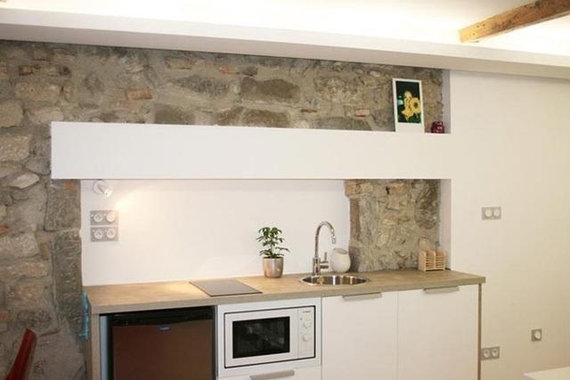 Dù nhà hẹp, chủ nhà vẫn bố trí được một khu bếp gọn gàng, đơn giản với hệ tủ kệ khép kín.