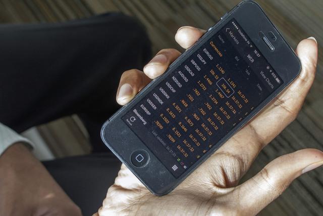 Agrawal dùng phần mềm trên điện thoại di động để nghe tỷ giá hối đoái. Ảnh: Prashanth Vishwanathan/Bloomberg