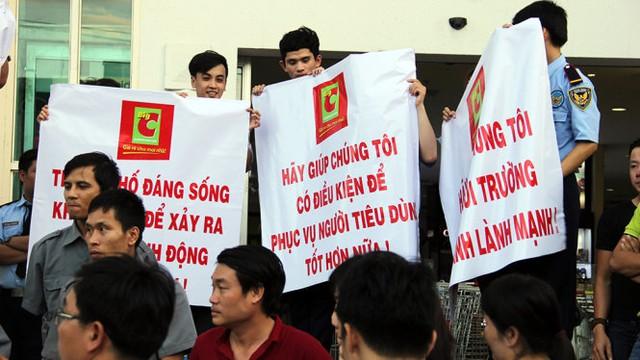 Nhân viên BigC đưa băng rôn biểu ngữ đề nghị TP Đà Nẵng can thiệp giải quyết các hành động cản trở kinh doanh tại tòa nhà Vĩnh Trung - Ảnh: TRƯỜNG TRUNG.