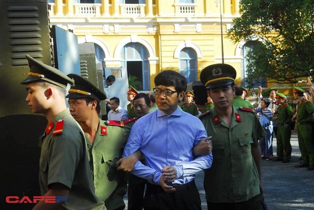 Trước giờ xét xử, Phan Thành Mai, nguyên Tổng giám đốc Ngân hàng Xây dựng xuất hiện trong chiếc áo dài tay màu xanh với cổ được cài kín và đôi tay bị còng.