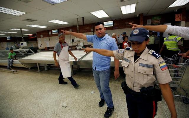 Nhân viên siêu thị và cảnh sát hướng dẫn người dân xếp hàng mua thực phẩm và hàng hóa thiết yếu tại một siêu thị ở Venezuela hôm 30/6 - Ảnh: Reuters.