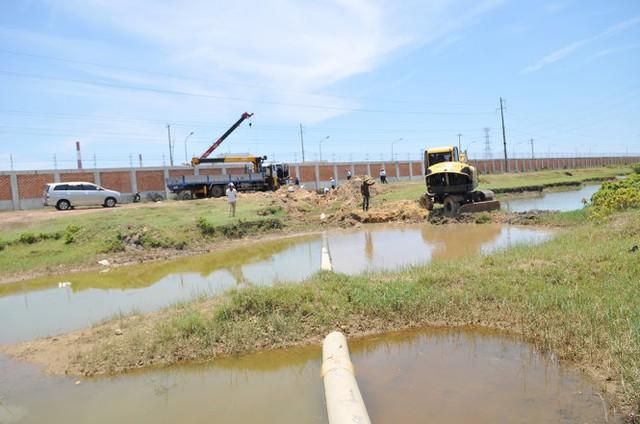 Các xe đào đang đào phần đường ống nối với mương xả lũ của phường Kỳ Phương - Ảnh: HỒ VĂN