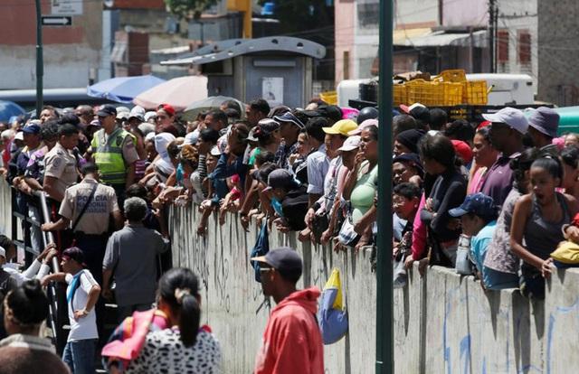 Cảnh xếp hàng chờ đến lượt vào mua bên ngoài một siêu thị ở Caracas - Ảnh: Reuters.