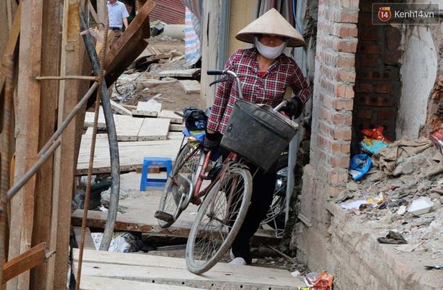Người phụ nữ này phải vác xe đạp đi qua lối đi gập ghềnh.