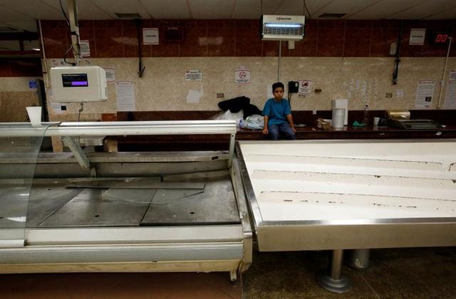 Một cậu bé ngồi bên quầy hàng thực phẩm lạnh trống trơn trong một siêu thị ở Caracas, Venezuela hôm 30/6 - Ảnh: Reuters.