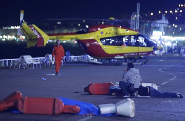 Trong bức ảnh là một người bị thương đang được nhân viên cứu hộ đưa về bệnh viện. Ảnh:ERIC GAILLARD/REUTERS.