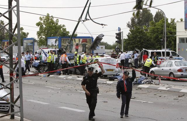 Cảnh sát Israel giải cứu người bị nạn sau khi một chiếc xe tải đâm liên tiếp vào xe buýt và ô tô tại Tel Aviv. Ảnh: AP