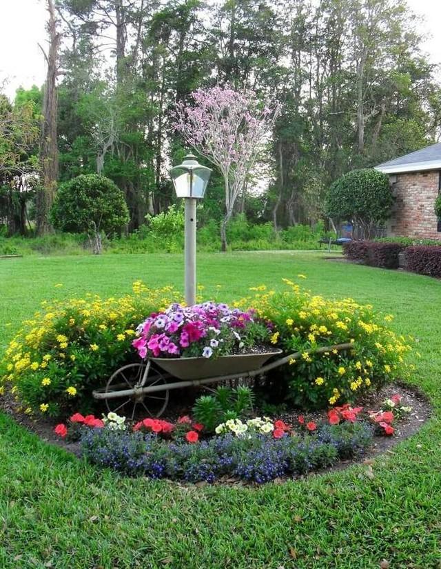 Một góc vườn lãng mạn với hoa lá bao quanh chiếc xe cút kít.
