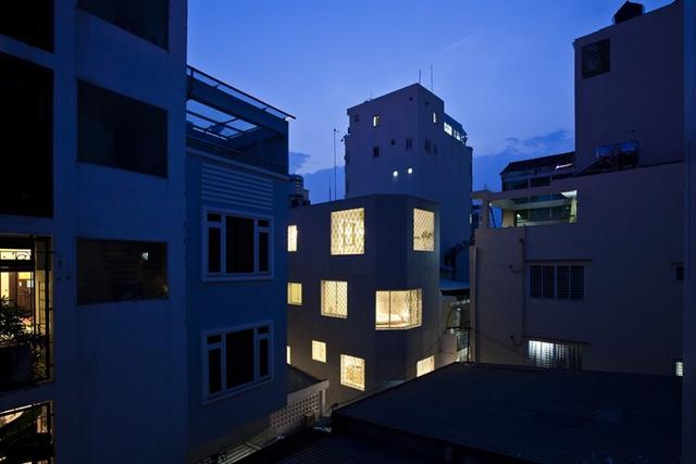 Căn nhà nhỏ nổi bật giữa con hẻm về đêm.