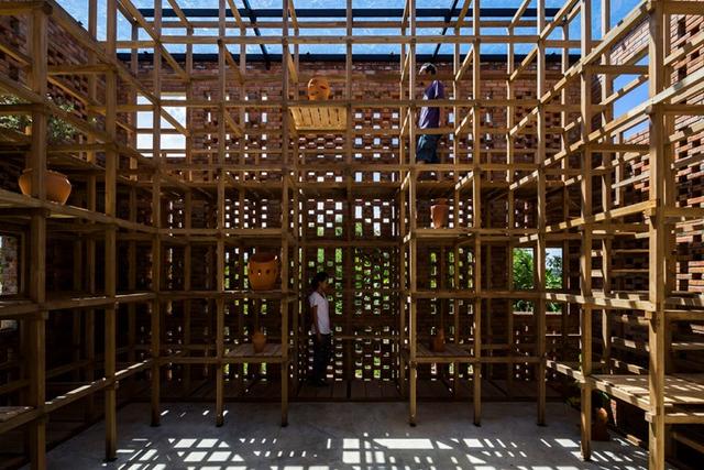 Hệ thống khung gỗ, giàn giáo khung tre bao quanh vừa có chức năng làm cầu thang, hành lang và đặt kệ để trưng bày những tác phẩm gốm sứ của chủ nhân.